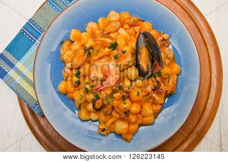 blue dish with gnocchi seafood and tomatoes sauce