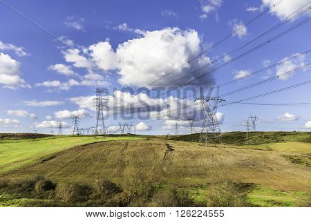 Lots of high voltage power transmission towers on a natural land with blue sky background