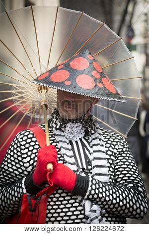 NEW YORK - MAR 27 2016: A man wearing a conical Asian style red and black hat holds a parasol on Easter Sunday at the traditional Easter Bonnet Parade along 5th Ave in Manhattan on March 27, 2016.