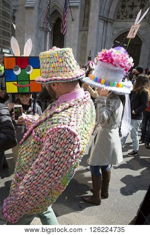 NEW YORK - MAR 27 2016: A man wearing a suit and hat made of candy corn takes pictures of parade goers on 5th Ave Easter Sunday at the traditional Easter Bonnet Parade in Manhattan on March 27, 2016.