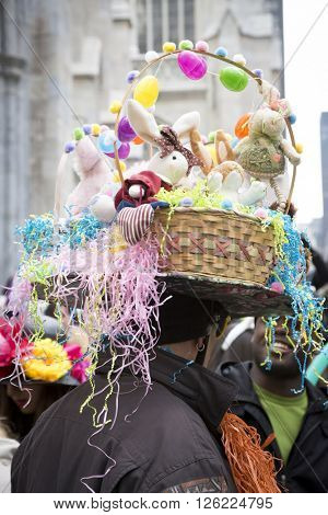 NEW YORK - MAR 27 2016: A man wearing a full Easter basket with straw as a bonnet walks along 5th Avenue on Easter Sunday for the traditional Easter Bonnet Parade in Manhattan on March 27, 2016.
