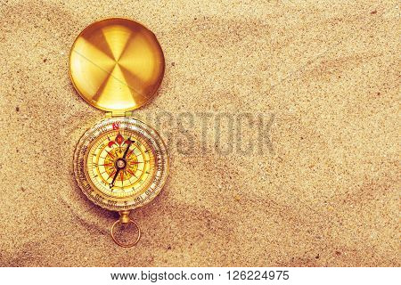 Top view of vintage compass in beach sand navigational equipment in warm brown sand of summer holiday vacation resort pointing to south.