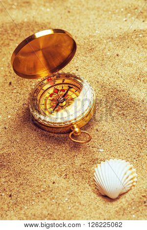 Top view of vintage compass and sea shell in beach sand navigational equipment in warm brown sand of summer holiday vacation resort pointing to south.