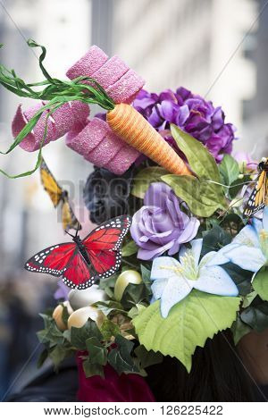 NEW YORK - MAR 27 2016: Close up of a bonnet with flowers, carrots, and butterflies worn by a parade goer on 5th Ave Easter Sunday at the traditional Easter Bonnet Parade, Manhattan on March 27, 2016.