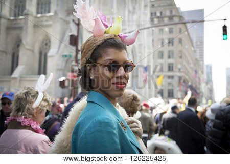 NEW YORK - MAR 27 2016: A woman wearing a decorative Easter bonnet with birds walks along 5th Avenue on Easter Sunday for the traditional Easter Bonnet Parade in Manhattan on March 27, 2016.
