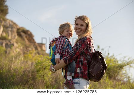 Beautiful family of mother and son walking near the sea