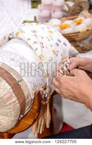 Woman hands embroider bobbin lace lace carefully.