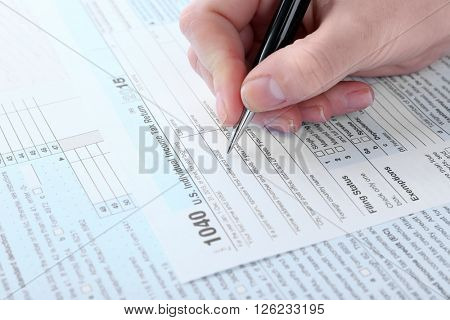 Female hand filling in the Income Tax Form, close up