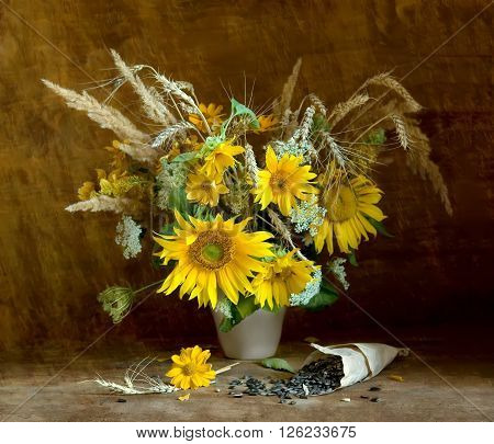 Autumn still life with bouquet of sunflowers in vase and seeds in paper bag on wooden background looking like a painting