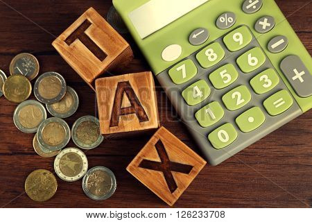 Word tax with coins and calculator on wooden table, top view