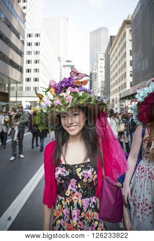 NEW YORK - MAR 27 2016: A woman wearing an Easter bonnet made of flowers and butterflies walks along 5th Ave on Easter Sunday for the traditional Easter Bonnet Parade in Manhattan on March 27, 2016.