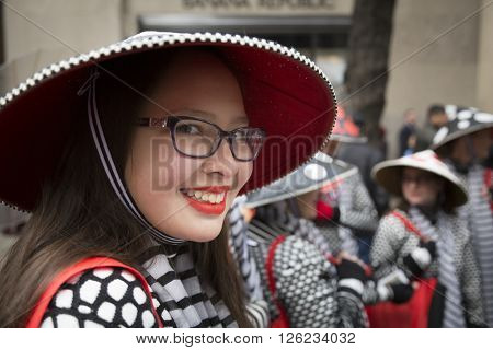 NEW YORK - MAR 27 2016: A woman wearing a conical Asian style red and black decorative hat on Easter Sunday at the traditional Easter Bonnet Parade along 5th Ave in Manhattan on March 27, 2016.