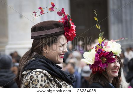 NEW YORK - MAR 27 2016: Two women wearing a elegant floral Easter bonnets walk along 5th Avenue on Easter Sunday for the traditional Easter Bonnet Parade in Manhattan on March 27, 2016.
