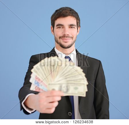 Attractive man in a suit holding fan of dollar and euro banknotes on blue background