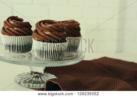 Three chocolate cupcakes on light table, close up