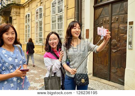 PRAGUE, CZECH REPUBLIC - AUGUST 18, 2015: woman taking selfie. A selfie is a self-portrait photograph, typically taken with a camera phone held in the hand or supported by a selfie stick.