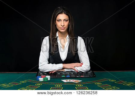 The beautiful girl, dealer, behind a table for game in poker
