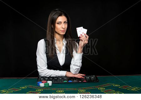 The beautiful girl, dealer, behind a table for game in poker, keeps the cards