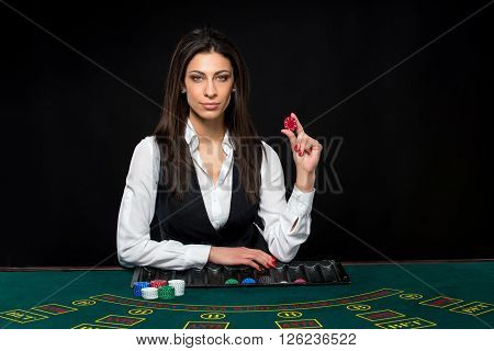 The beautiful girl, dealer, behind a table for game in poker, hold chips in hands