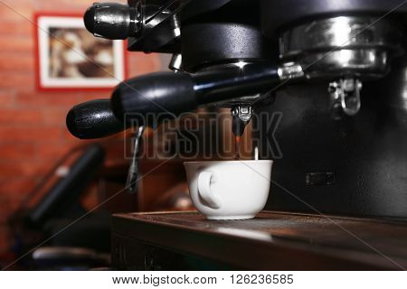 Fresh coffee making in the professional coffee machine, close up