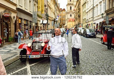 PRAGUE, CZECH REPUBLIC - AUGUST 18, 2015: man taking a selfie. A selfie is a self-portrait photograph, typically taken with a camera phone held in the hand or supported by a selfie stick.
