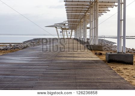 Wooden pier with weathered sunshades and boulders levee on early morning at Dead Sea
