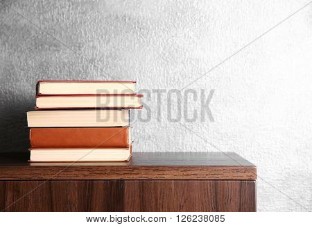 Stack of books on wooden commode over grey wall background