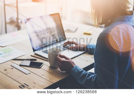 Working process modern office. Account manager working with new business project. Typing contemporary laptop, varios photo screen, on smartphone wood table. Horizontal. Film and flares effects