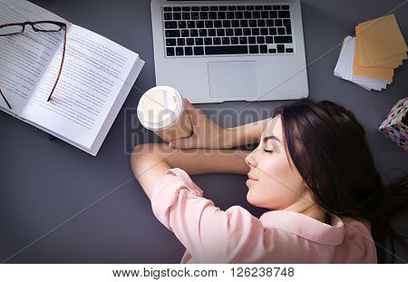 Young woman with cup of coffee fell asleep while using laptop at the table