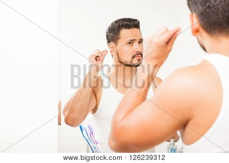 Handsome Man Cleaning His Ears With A Swab