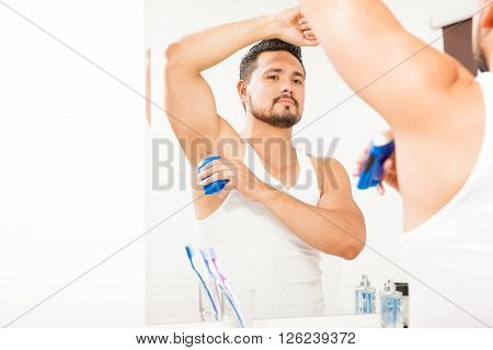 Young Man Putting On Deodorant In The Bathroom