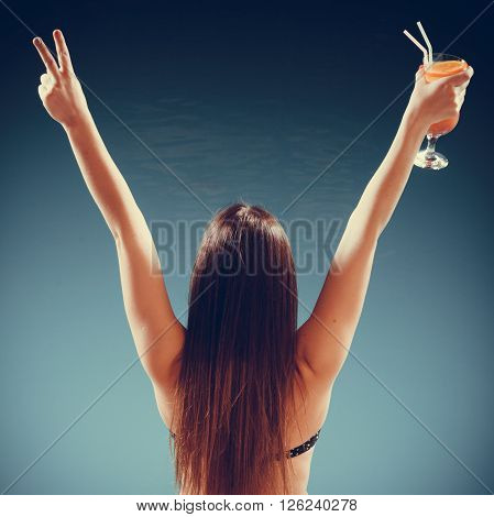 Spa relax and holidays concept. Happy woman in swimsuit back view. Fit female body girl long hair at poolside with cocktail glass arms raised up in celebration