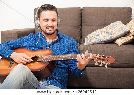 Hispanic Man Playing The Guitar With Headphones