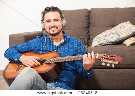 Happy Male Musician Playing The Guitar At Home