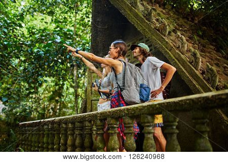 tourists in thailand on top of ancient jungle ruins