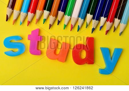 Study word with colorful pencils on yellow background