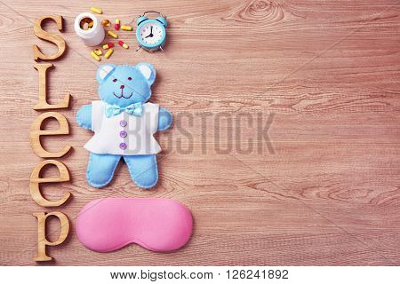 Word Sleep with pills, little toy and sleeping mask on a wooden background