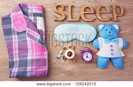 Word Sleep with pajamas, little toy and sleeping mask on a wooden background