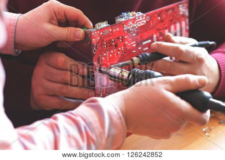 Two workers soldering electronic board selective focus