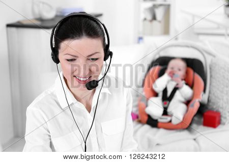 Businesswoman with baby boy working from home using laptop and headset