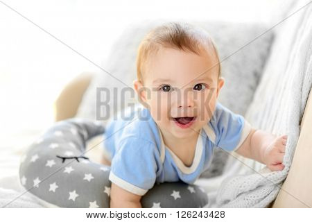 Little baby boy crawling on a couch at home