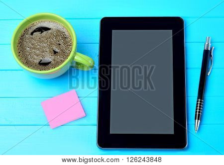 Tablet pc with coffee cup and notes on blue wooden table