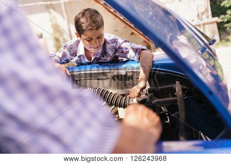 Family and Generation gap. Old grandpa spending time with his grandson. The senior man teaches to the preteen child to fix the engine of a vintage car from the 60s. They smile happy.
