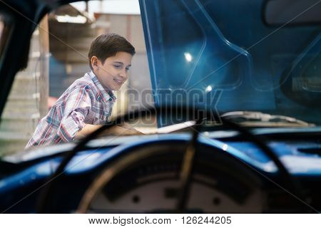 Preteen child looking at the engine of a vintage car from the 60s. He is amazed and excited. The boy smiles happy and leans against the open hood. Viewed from the interior of the car.