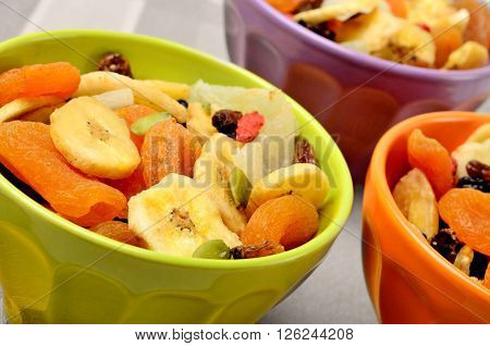 Colorful bowl with dried fruits on table