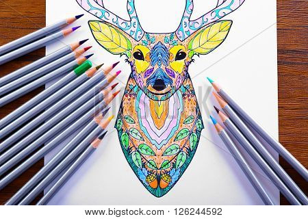 Adult anti stress coloring with crayons on wooden table, top view