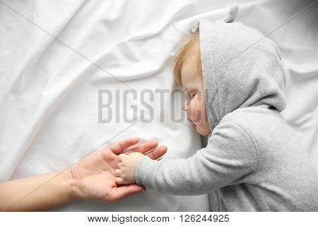 Hands of mother and her little baby boy on the bed, close up