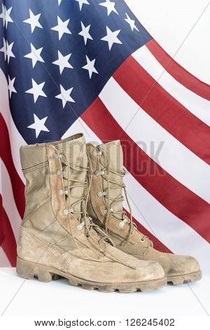 Old combat boots with American flag in the background