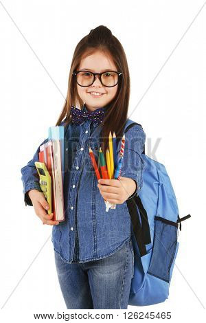 Little girl with backpack holding school stationery isolated on white