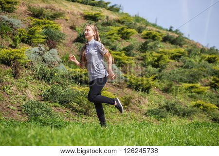 Photo of happy long-haired young blonde woman doing running activities. ** Note: Soft Focus at 100%, best at smaller sizes